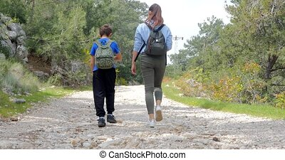 Young woman with boy walking on the road - Young woman with...