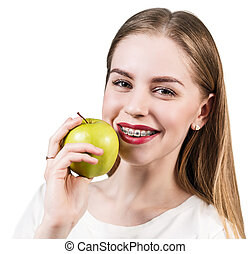 Young woman with brackets on teeth eating apple