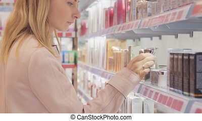 Young woman with braid chooses perfume in small shop