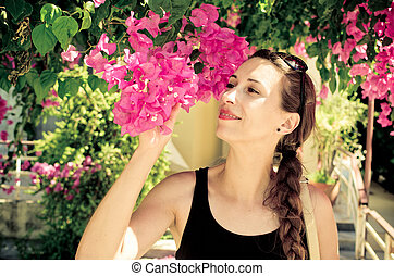 Young woman with braid smelling pink flowers
