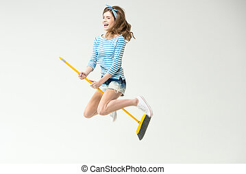 Young woman with broom - Happy beautiful young woman flying...