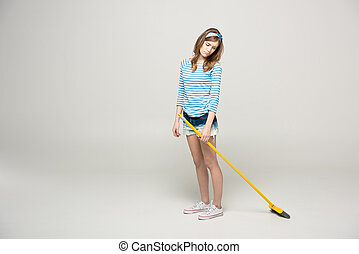 Young woman with broom - Upset young woman standing with...