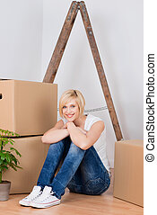 Young Woman With Cardboard Boxes Sitting On Hardwood Floor