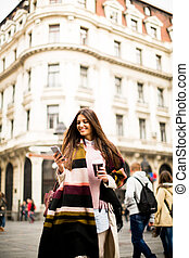 Young woman with cell phone walking on the street