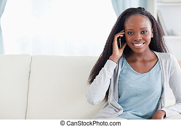Young woman with cellphone on the sofa