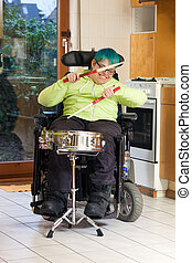 Young woman with infantile cerebral palsy caused by complications at birth sitting in a multifunctional wheelchair playing a drum for spastic therapy with a happy smile