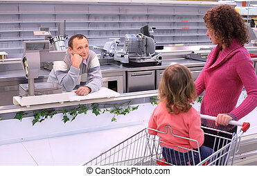 young woman with child and bored seller in shop with empty...