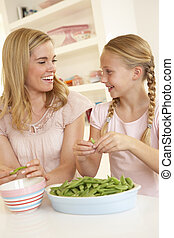 Young woman with child splitting pea in kitchen