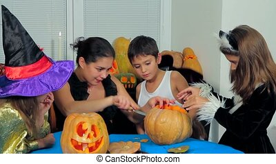 Young Woman With Children Carving Halloween Pumpkins