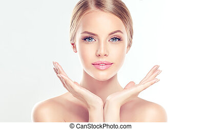 Portrait of beautiful Young Woman with clean, fresh, skin touching her face. Facial treatment. Cosmetology, beauty and spa.