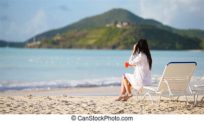 Young woman with cocktail glass on white beach sitting on...