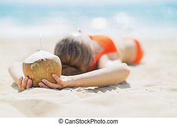 Young woman with coconut relaxing on beach