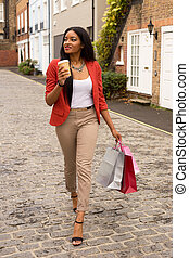 young woman with coffee and shopping bags