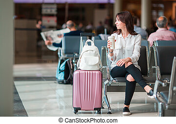Young woman with coffee in an airport lounge waiting for flight aircraft.