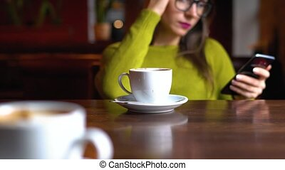 Young woman with coffee using smartphone in cafe