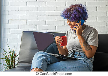 young woman with computer, mobile phone and cup on the sofa