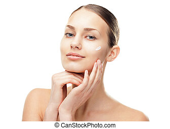 Young woman with cosmetic cream on a cheek - Closeup...