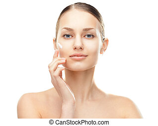 Young woman with cosmetic cream on a cheek - Closeup ...