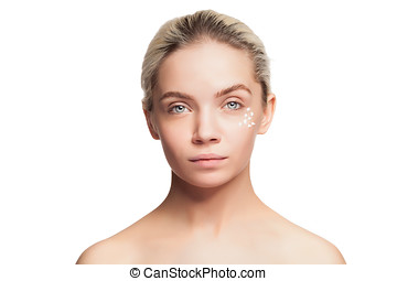 Young woman with cream drops on face on white background