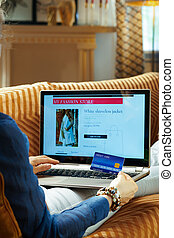 young woman with credit card buying clothes online