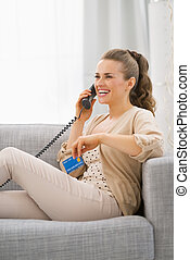 Young woman with credit card sitting on divan and talking phone