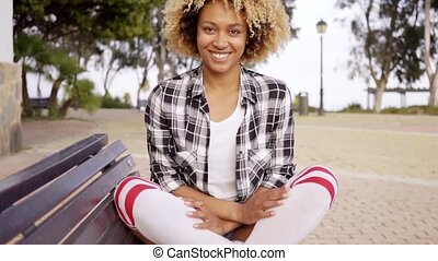 Young woman with crossed legs on bench