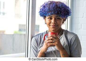young woman with cup of coffee at the window