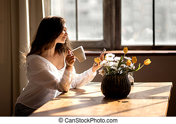 Young woman with cup of coffee is stare at the phone at kitchen