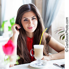 young woman with cup of latte or cappuccino coffee in cafe