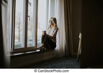 Young woman with cup of tea or coffee sitting and drinking on the window sill at home