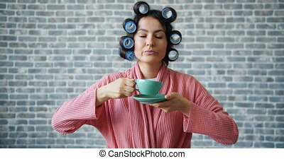 Young woman with curlers on hair holding cup drinking coffee...