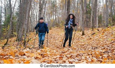 Young woman with curly hair and a boy on scandinavian walk....