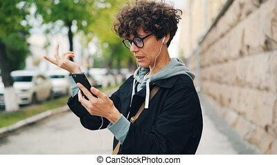 Young woman with curly hair and glasses is talking to friends online standing outdoors and using smartphone and earphones. Gadgets, internet and communication concept.