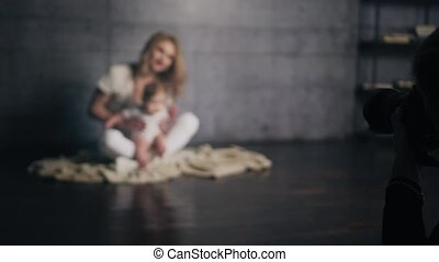 Young woman with curly hair is kissing her little kid on the...