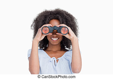 Young woman with curly hair looking through binoculars...