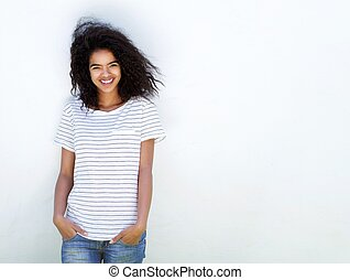 Young woman with curly hair smiling against white background