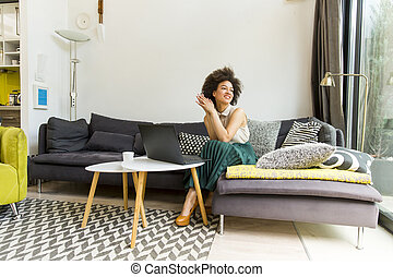 Young woman with curly hair, uses laptop and sitting on the sofa at home