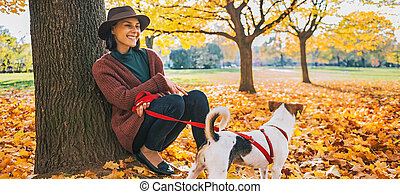 Young woman with cute dog sitting under tree in autumn park