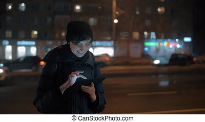 Young woman with digital tablet in evening city