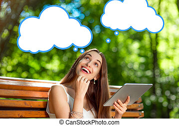 Young woman with digital tablet in the park