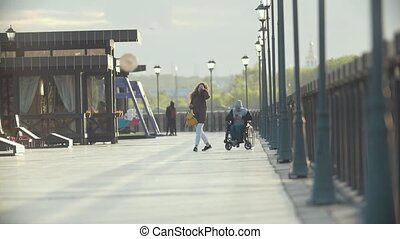Young woman with disabled man in a wheelchair spending time together on the quay