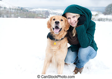 young woman with dog in the snow