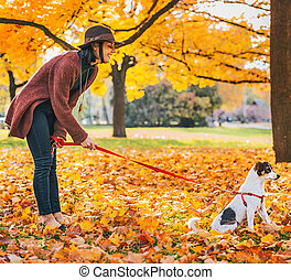 Young woman with dog outdoors in autumn