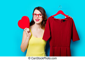 young woman with dress on hanger and toy