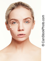 Young woman with drops of cream on her face