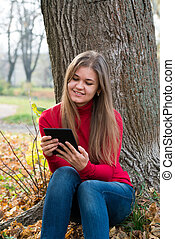 Young woman with E-book in autumn park