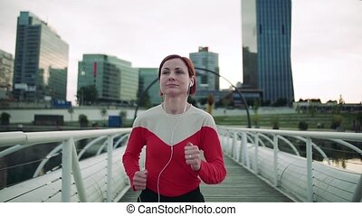 Young woman with earphones running on bridge outdoors in ...