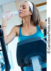 Young woman with elliptic machine drinking water in the gym.