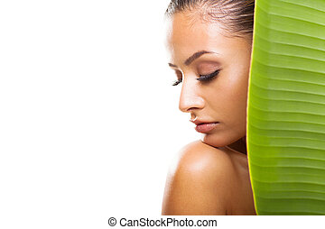 young woman with eyes closed behind large green leaf