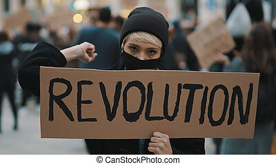 Young woman with face mask and banner protesing in the crowd. Revoultion concept.